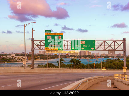 Road signs for Miami Beach, Florida, USA, at MacArthur Causeway at sunset. - Stock Photo