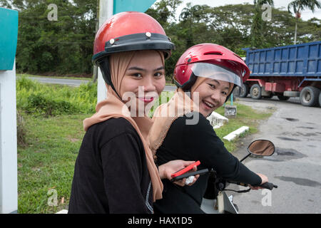 Two identically dressed Muslim girls, sit on a motor scooter in Mukah, Mukah Division, Sarawak, Malaysia - Stock Photo