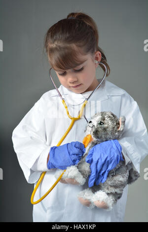 Little child (girl age 6) who wants to be a veterinarian play pretend to be an animal doctor in veterinary clinic. - Stock Photo