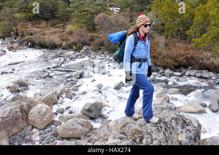 Woman hiker crossing a frozen stream in Tongariro National Park rain forest  in the North Island of New Zealand. - Stock Photo