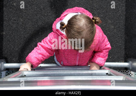 Flat lay view of a little girl (age 2) climbs on a ladder in a playground. Early childhood development concept. - Stock Photo