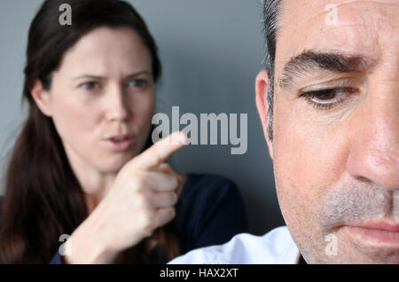 Portrait of woman blaming her husband. Unhappy couple who have fallen out over a disagreement. Man in the front - Stock Photo