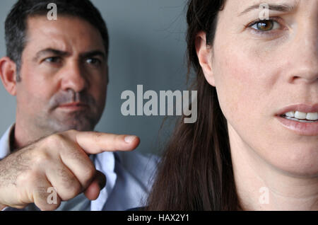 Portrait of a man blaming his wife. Unhappy young who have fallen out over a disagreement. Woman in the front and - Stock Photo