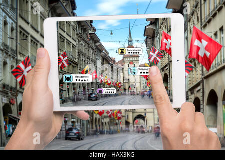 Hand holding smart phone use AR application to check relevant information about the spaces around customer. Bern - Stock Photo