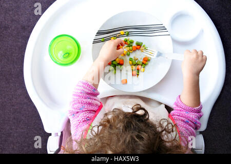 Above view of a little toddler child eats vegetables. Childhood and children health care concept. Real people. copy - Stock Photo