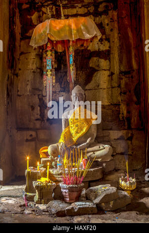 Statue of Buddha wrapped in silken robe inside the main temple at the ancient, 12th century religious site of Angkor - Stock Photo