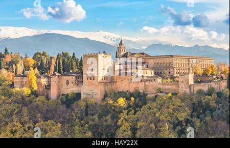 Alhambra - medieval Moorish fortress surrounded by yellow autumn trees with snow mountains on background, Granada, - Stock Photo