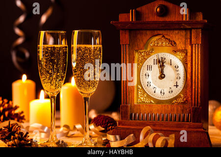 Two glasses of champagne and a vintage clock at a New Years Eve party. - Stock Photo