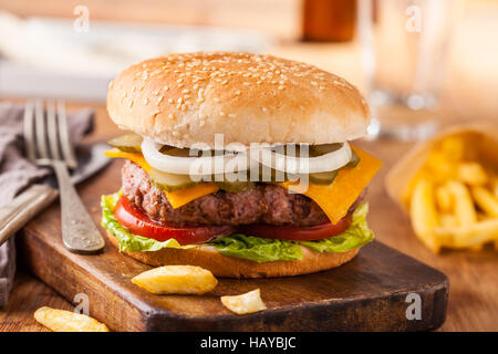 Appetizing hamburger with fries, beer on wooden cutting board. Pickles, onion, and cheddar cheese. - Stock Photo