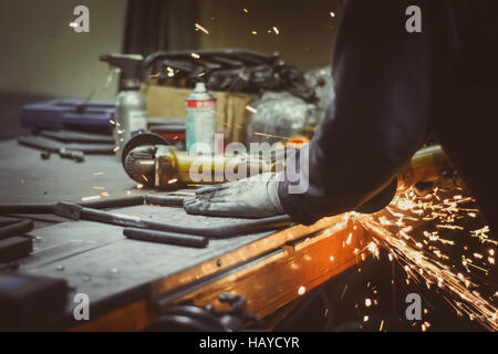 Worker cutting pieces of round pipe with an angle grinder on a busy workshop table, producing sparks - Stock Photo