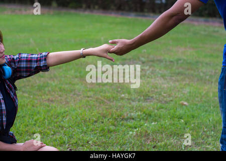Woman sitting on the grass reaching to shake the hand of man. helping hand and love concept. - Stock Photo