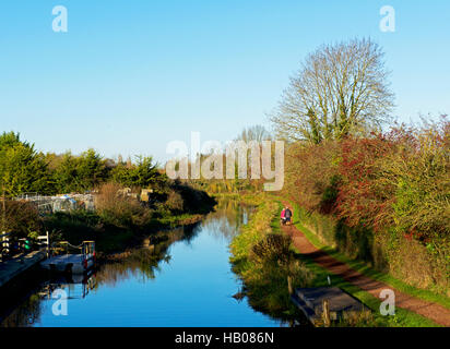 Couple walking along the towpath of the Bridgwater and Taunton Canal, near Maunsel Lock, Somerset, England UK - Stock Photo
