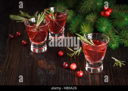 Christmas refreshing alcoholic drink with cranberries and rosemary on wooden background, with fir branches - Stock Photo