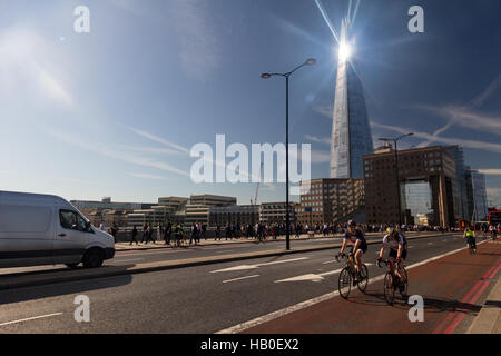 London Bridge traffic during the morning commute, with the sunlight gleaming off the Shard building in the background. - Stock Photo