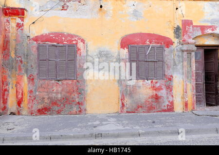 Yellow-ocher and vermilion facade of old French colonial house showing chipped areas along paint-faded zones and - Stock Photo
