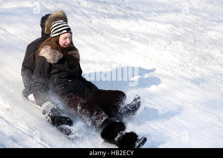 Laughing girl and a boy sliding down the hill on a toboggan dish - Stock Photo