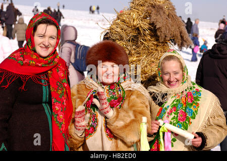 Three women in traditional Ukrainian clothes and a straw man behind them to be burnt on Shrovetide as a symbol of - Stock Photo