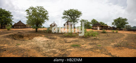 Panorama of Himba village with traditional huts near Etosha National Park in Namibia, Africa - Stock Photo