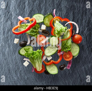 flying salad on slate background - Stock Photo