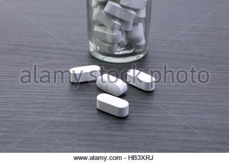 Old glass bottle full of pills large - Stock Photo