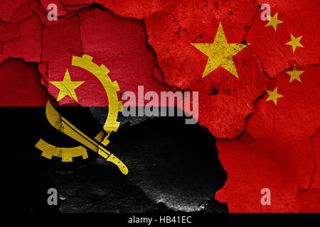 flags of Angola and China painted on cracked wall - Stock Photo