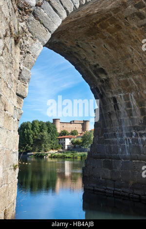 Valdecorneja Castle seen through an arch of the Romanesque bridge across the River Tormes,  at El Barco De Avila, - Stock Photo