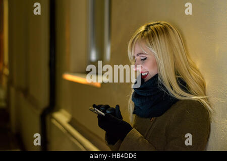 Smiling woman using smartphone at night - Stock Photo