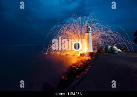 Burning steel wool spinned near the lighthouse - Stock Photo