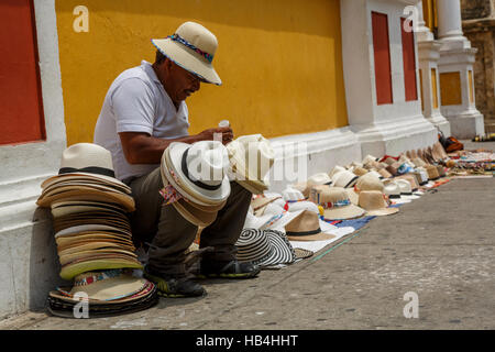 A man sitting amongst his hats for sale on the pavement in a street in Cartagena, Bolivar, Colombia - Stock Photo