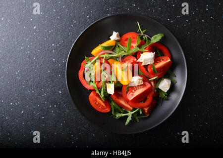 Fresh salad on black plate, food top view - Stock Photo