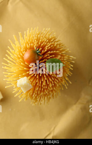 Raw spaghetti with tomato and cheese, food top view - Stock Photo