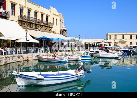 View of boats and waterfront restaurants in the inner harbour, Rethymno, Crete, Greece, Europe. - Stock Photo