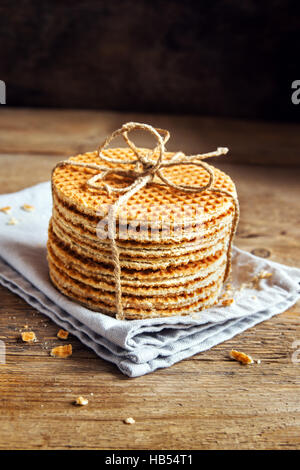 Stack of traditional dutch caramel waffles tied up with jute twine on rustic wooden background, selective focus - Stock Photo