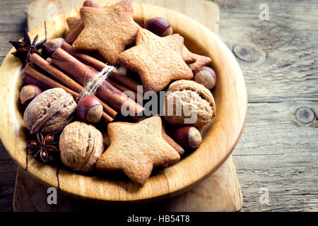 Rustic Christmas decoration with gingerbread cookies, nuts and Christmas spices on wooden plate close up - Stock Photo