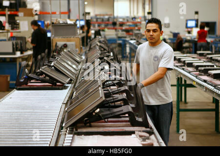 A worker pushes flat screen computer monitors down the line for recycling at a computer recycling company in Austin, - Stock Photo