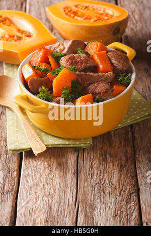 Beef stew with pumpkin, onion and spices close up in a yellow pan on the table. vertical - Stock Photo