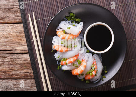 Japanese food: Shirataki with prawns, spring onions and soy sauce on a plate close-up. Horizontal view from above - Stock Photo