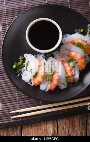 Japanese food: Shirataki with prawns, spring onions and soy sauce on a plate close-up. vertical view from above - Stock Photo