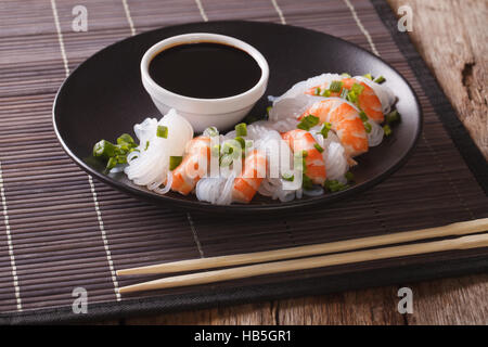 Japanese food: Shirataki with prawns, spring onions and soy sauce on a plate close-up. horizontal - Stock Photo
