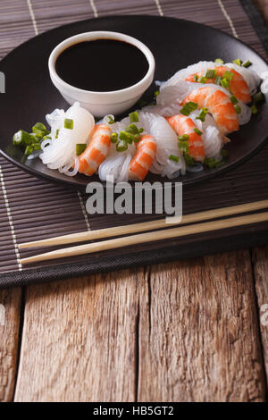 Japanese food: Shirataki with prawns, spring onions and soy sauce on a plate close-up. Vertical - Stock Photo