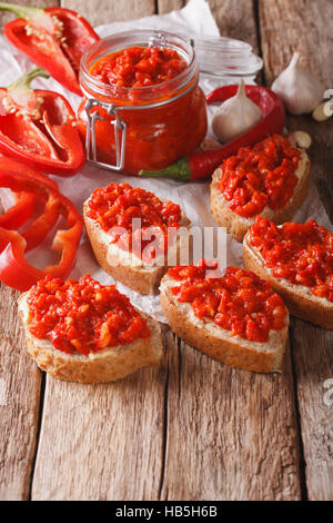 Ajvar in a glass jar and toast on a wooden background. Vertical, rustic - Stock Photo