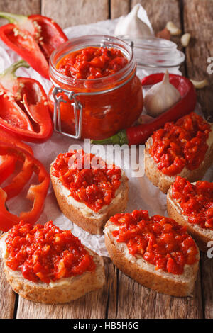 Relish (Ajvar) of Roasted Red Bell Peppers on toast slices close-up on the table. Vertical - Stock Photo
