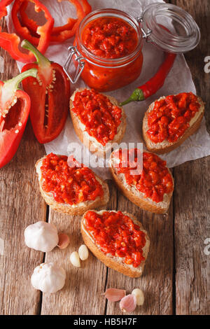 Ajvar - delicious dish of red peppers, onions and garlic closeup on the table. vertical - Stock Photo