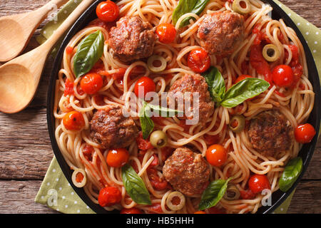 Italian food: spaghetti with meatballs, olives, basil and tomato sauce closeup on a plate. Horizontal view from - Stock Photo