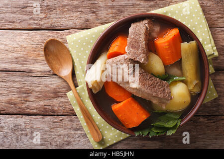 Delicious Pot-au-feu beef soup with vegetables close up in a bowl on the table. horizontal view from above - Stock Photo