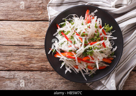 Fresh salad of daikon with pepper and herbs closeup on a plate. horizontal view from above - Stock Photo