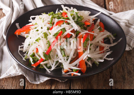 Tasty salad of daikon with pepper and herbs closeup on a plate. horizontal - Stock Photo