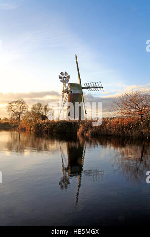 A view of Turf Fen Drainage Mill with reflections in the River Ant on the Norfolk Broads at Ludham, Norfolk, England, - Stock Photo