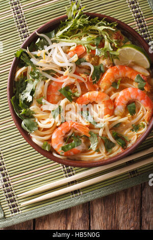 Malaysian laksa soup with prawns close up in a bowl on the table. vertical view from above - Stock Photo