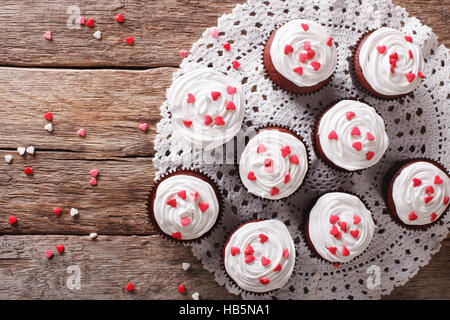 tasty red velvet cupcakes on a lacy napkin close-up on the table. Horizontal view from above - Stock Photo